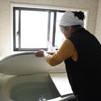 買ったばかりの機械を入れて風呂の水を沸かそうとする松本キミさん。温まるまで7、8時間待たなければいけないという=福島県矢祭町高地原地区で2019年10月19日午前11時14分、古川幸奈撮影