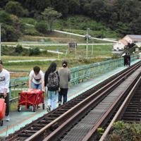 孤立した高地原地区の集落のためボランティアがJRの鉄橋を歩いて渡り、水20リットルの入ったポリタンクを運んでいた=福島県矢祭町で2019年10月20日午後0時26分、古川幸奈撮影
