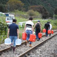 孤立した高地原地区の集落へつながる線路を歩いて水を運ぶボランティア=福島県矢祭町で2019年10月20日午後0時33分、古川幸奈撮影