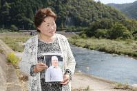 Sawako Nakatsu raises a photo of her late husband Shoshi, who claimed he was exposed to radioactive