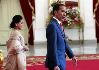 Indonesian President Joko Widodo walks with his wife prior to receiving guests ahead of his presidential inauguration for his second term, at Merdeka Palace in Jakarta, Indonesia, Sunday, Oct. 20, 2019. (AP Photo/Dita Alangkara)