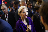 In this Oct. 15, 2019, photo, Democratic presidential candidate Sen. Elizabeth Warren, D-Mass., speaks in the spin room following a Democratic presidential primary debate at Otterbein University in Westerville, Ohio. The Democratic presidential candidates are not talking much about impeachment as they campaign. (AP Photo/John Minchillo)