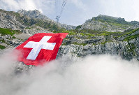 This July 31, 2009 file photo shows the world's largest Swiss flag hanging on the rock face of the mountain Saentis in Schwaegalp, Switzerland, (Ennio Leanza/Keystone via AP)