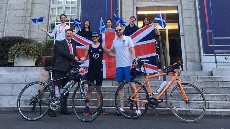 英国大使館に戻り、祝福を受けるデービッドさん(前列中央)とジェームズさん(同右)。同左はポール・マデン駐日英大使