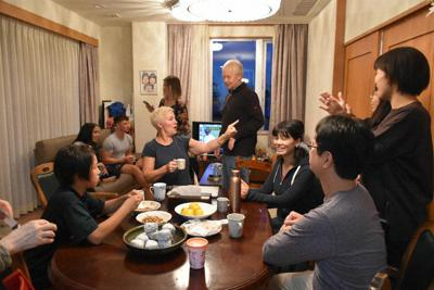 打ち解けた様子で語り合う久喜さん一家と外国人宿泊者たち=岩手県釜石市の久喜さん宅で