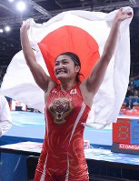 2012 London Olympics -- Japan's Kaori Icho holds up her national flag after winning her third consecutive gold medal in the 63-kilogram division in women's wrestling. After the competition she revealed that she had suffered ruptured ankle ligaments but didn't show any pain while competing. (Mainichi/Masaru Nishimoto)