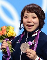 2012 London Olympics -- Japan's Hiromi Miyake smiles as she shows off her silver medal she captured in the 48-kilogram division in women's weightlifting. Miyake's achievement marked the first time a Japanese woman had earned a medal in the sport. She lifted 87 kilograms in the snatch and 110 kilograms in the clean and jerk. (Mainichi/Ryoichi Mochizuki)