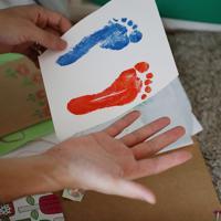 「こんなに大きくなっていたんだ」。松永さんは、莉子ちゃんの足形と自分の手の大きさを比べ、つぶやいた=東京都豊島区で2019年9月16日、小川昌宏撮影