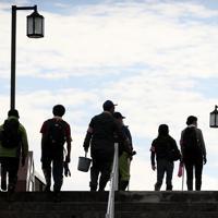 バケツや手袋を持ち、安達太良川にかかる橋を渡るボランティアの人たち=福島県本宮市で2019年10月20日午後1時32分、吉田航太撮影