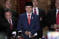 Indonesian President Joko Widodo, center, smiles as he speaks to the media upon arrival after his inauguration for his second term, at Merdeka Palace in Jakarta, Indonesia, on Oct. 20, 2019. (AP Photo/Dita Alangkara)