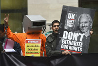 Supporters of Wikileaks founder Julian Assange demonstrate oustide Westminster Magistrates' Court in London where Assange is expected to appear as he fights extradition to the United States on charges of conspiring to hack into a Pentagon computer, in London, on Oct, 21, 2019. (Kirsty O'Connor/PA via AP)
