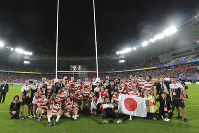 Japan players pose for a group photo after the Rugby World Cup quarterfinal loss to South Africa at Tokyo Stadium in Tokyo, Japan, on Oct. 20, 2019. (AP Photo/Eugene Hoshiko)