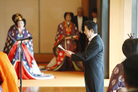 Prime Minister Shinzo Abe, right, delivers a congratulatory statement after Japan's Emperor Naruhito proclaimed his ascension to the Chrysanthemum Throne at the Imperial Palace in Tokyo's Chiyoda Ward, on Oct. 22, 2019. (Pool photo)