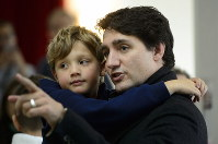 Canadian Prime Minister Liberal Leader Justin Trudeau holds his son Hadrien as he waits to vote in Montreal, on Oct. 21, 2019. (Paul Chiasson/The Canadian Press via AP)