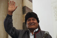 Bolivian President Evo Morales waves to supporters at the presidential palace in La Paz, Bolivia, after a first round presidential election, on Oct. 20, 2019. (AP Photo/Jorge Saenz)