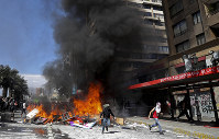 Anti-government protesters create burning roadblocks amid ongoing demonstrations triggered by an increase in subway fares in Santiago, Chile, on Oct. 21, 2019. (AP Photo/Miguel Arenas)