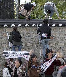 In this Oct. 18, 2019 photo, college students use ladders to climb walls of the U.S. ambassador's residence in Seoul, South Korea. (Kim Sun-ung/Newsis via AP)
