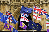 Various flags flutter in the wind outside the houses of Parliament in London, on Oct. 21, 2019. (AP Photo/Alberto Pezzali)