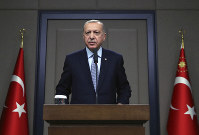 Turkish President Recep Tayyip Erdogan talks to reporters before traveling to Russia to meet with Russian President Vladimir Putin, in Ankara, on Oct. 22, 2019. (Presidential Press Service via AP, Pool)