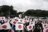 People wave Japanese flags as they gather to celebrate outside the Imperial Palace after the enthronement ceremony for Emperor Naruhito, on Oct. 22, 2019, in Tokyo. (AP Photo/Jae C. Hong)