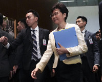 In this Oct. 17, 2019, file photo, Hong Kong Chief Executive Carrie Lam, center, arrives at chamber of the Legislative Council in Hong Kong. (AP Photo/Vincent Yu)