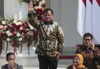 Newly appointed Defense Minister Prabowo Subianto who is the former rival of Indonesian President Joko Widodo in last April's election, waves as he is introduced during the announcement of the new cabinet at Merdeka Palace in Jakarta, Indonesia, on Oct. 23, 2019. (AP Photo/Dita Alangkara)