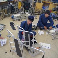 熱心に車いすを整備するVYS部の部員たち=新居浜工業高提供提供