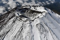 Mount Fuji is seen covered with snow from a Mainichi Shimbun helicopter over the central Japan city of Fujiyoshida, Yamanashi Prefecture, on Oct. 23, 2019. The first snow heading into winter was observed on the mountain the previous day by the Kofu Local Meteorological Office. (Mainichi/Kaho Kitayama)