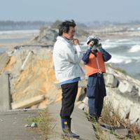 震災発生200日の行方不明者集中捜索を見つめる大久保三夫さん(左)。行方不明の一人娘、真希さんの発見を願っているが「今日も出てきてくれないのかな」とつぶやいた=宮城県山元町で2011年9月28日午後1時55分、丸山博撮影