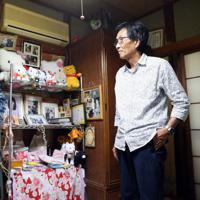 猪野詩織さんの遺影を見つめる父憲一さん。写真は詩織さんが好きだったヒマワリで飾られている=埼玉県上尾市で2019年10月3日、小川昌宏撮影
