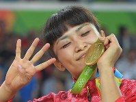 2016 Rio de Janeiro Olympics -- Japan's Kaori Icho kisses her gold medal during the award ceremony for the 58-kilogram division in the women's wrestling while raising her four fingers to show that she has won four consecutive Olympic gold medals, the first time a woman had achieved the individual feat in Olympic history. (Mainichi/Daisuke Wada)