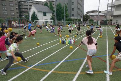 プレーリーダーの教員とともに姴ボールで遊ぶ児童たち=足立小学校で(同校提供)