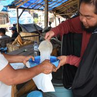 漏斗でビニール袋になみなみと注ぎ入れるバロ売りの男性(右)=インドネシア中部スラウェシ島の北トラジャ県で2019年9月21日、武内彩撮影