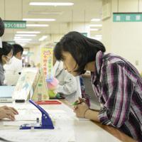 福島県本宮市の職員から借り上げ住宅の制度などについて説明を受ける人たち=同市役所で