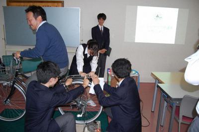 理科クラブの発表で小水力発電の実演をする部員らと、自転車をこぐ先生=埼玉県春日部市の松実高等学園で