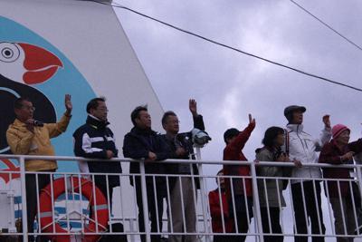 岸壁で見送る市民らに手を振る北方領土観光ツアーの参加者=北海道根室市の根室港で29日午後2時59分