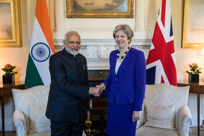 メイ前英首相(右)と握手するインドのモディ首相(Bloomberg)