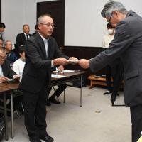 県商工労働部の河村理事(右)に申し入れ書を手渡す「上関原発を建てさせない祝島島民の会」の清水代表