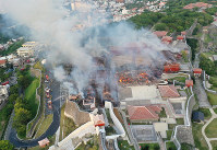 The main hall, center, and the north hall, left, of Shuri Castle in the Okinawa Prefecture capital of Naha are seen burning on the morning of Oct. 31, 2019. (Photo courtesy of Ryukyu Shimpo)