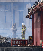 A firefighter stands in front of the Seiden main hall of Shuri Castle in Naha, Okinawa Prefecture, southern Japan, on Oct. 31, 2019, after it was razed by a fire that broke out at the historic World Heritage-listed site earlier in the day. (Kyodo)