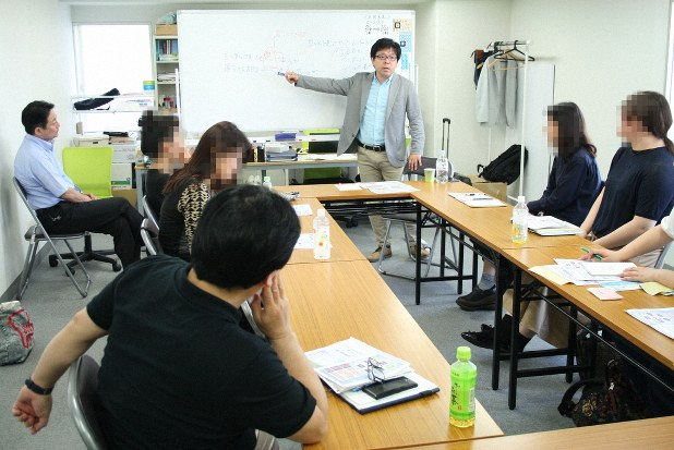 ワンネスグループの相談所を訪れたギャンブル依存症患者の家族やパートナーらに依存症について説明する三宅さん(奥中央)=横浜市内で
