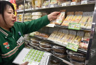 A Seven-Eleven store manager places barcode stickers on sandwiches subject to point rewards in Higashidaikumachi, Tokushima, on Oct. 30, 2019. (Mainichi/Sakura Iwamoto)