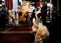 A man wearing a Halloween costume voluntarily picks up trash from the street in Tokyo's Shibuya Ward on Oct. 31, 2019. (Mainichi/Daiki Takikawa)