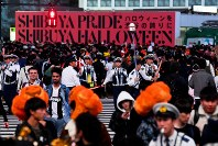 People wearing Halloween costumes cross a street in front of Shibuya Station in Tokyo's Shibuya Ward while following instructions given by police officers on Oct. 31, 2019 (Mainichi/Daiki Takikawa)