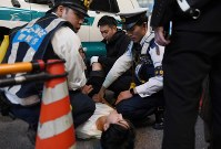 Police officers check on a man's condition after finding him collapsed in the street in Tokyo's Shibuya Ward on Oct. 31, 2019. (Mainichi/Daiki Takikawa)