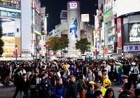 People wearing Halloween costumes gather around Shibuya Station as police officers patrol the area in Tokyo's Shibuya Ward on Oct. 31, 2019. (Mainichi/Daiki Takikawa)