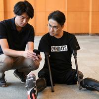 歩行訓練後に練習の様子を撮影した動画を確認する乙武洋匡さん(右)=東京都文京区、内藤絵美撮影