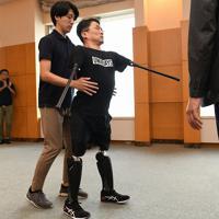 義足を装着して歩行訓練をする作家の乙武洋匡さん(中央)=東京都文京区で、内藤絵美撮影