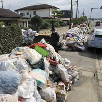 県道沿いにある民家前の歩道に積み上げられた災害ごみ。処理のめどが立っていない=福島県郡山市水門町で2019年10月30日、梅村直承撮影