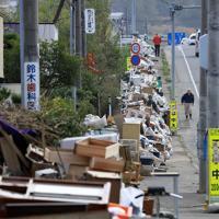 県道沿いにある民家前の歩道に積み上がられた災害ごみ。処理のめどがたっていない=福島県郡山市水門町で2019年10月30日、梅村直承撮影